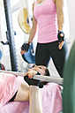 Two women doing barbell bench presses in a power rack - MADF000733