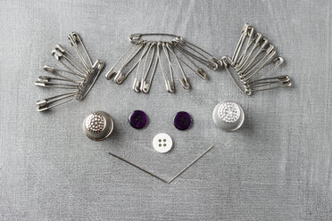 Smiling face of a girl built of sewing items on grey background - MYF001249
