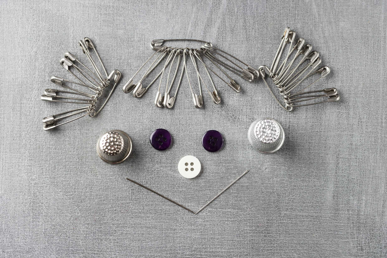 Smiling face of a girl built of sewing items on grey background - MYF001249 - Mandy Reschke/Westend61