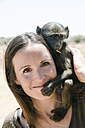 Namibia, portrait of smiling woman with baby baboon on her shoulder - GEMF000502