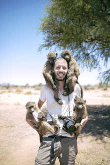Namibia, man with camera holding four baby baboons - GEMF000505