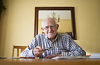 Portrait of smiling senior man with magnifier sitting at a table - RAEF000682