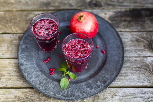 Pomegranate sirup with pomegranate seeds, prosecco and mineral water in glasses - SARF002338