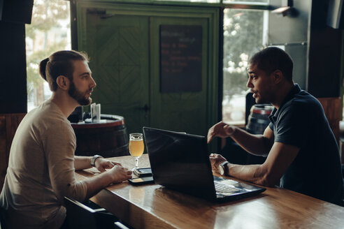 Two men with laptop sitting in a bar talking - ZEDF000006