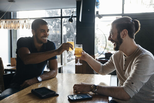 Two happy men in a bar clinking beer glasses - ZEDF000009