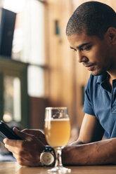 Man using digital tablet in a bar - ZEDF000012