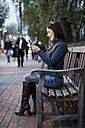 Happy woman looking at smartphone on a bench - MAUF000092