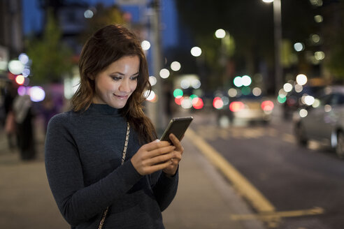Woman checking her smartphone by the roadside - MAUF000095