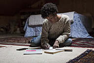 Young woman at home sitting on floor writing - MAUF000113