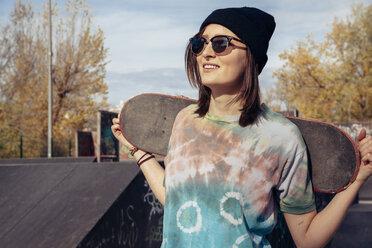 Smiling young woman holding skateboard at skatepark - ZEDF000020