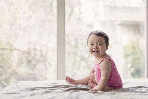 Portrait of happy baby girl sitting on bed in front of a window - LITF000008