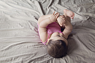 Baby girl lying on bed playing with her foot - LITF000011