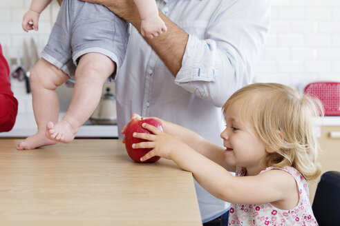 Toddler girl in kitchen holding apple with family in background - LITF000014