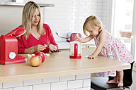 Mother and little daughter in the kitchen preparing apple sauce together - LITF000017