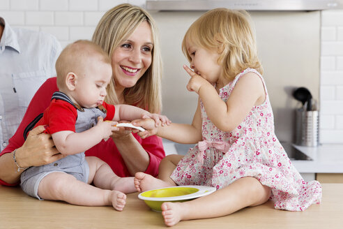 Smiling mother with baby and toddler girl in the kitchen - LITF000020
