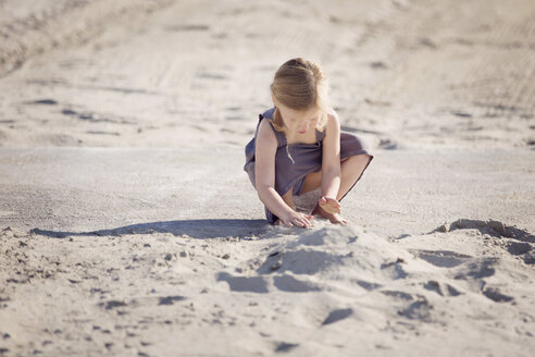 Little girl playing in the sand on the beach - LITF000026