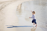 Toddler running at seafront playing with his shadow - LITF000029