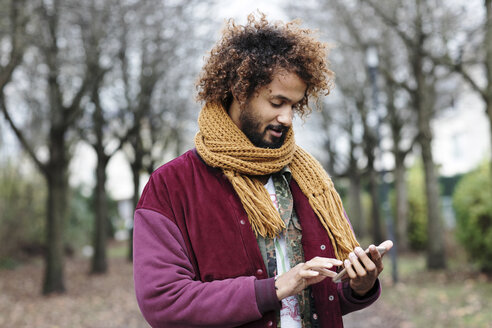 Portrait of man with dyed ringlets wearing scarf using his smartphone - GDF000904