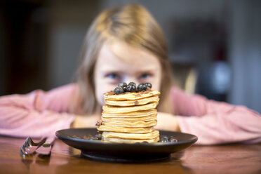 Plate with stack of pancakes with little girl in the background - SARF002357