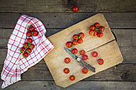 Kitchen towel and sliced and whole tomatoes on chopping board - LVF004208