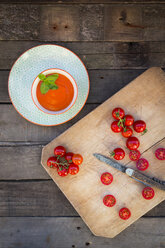 Bowl of tomato cream soup and chopping board with whole and sliced tomatoes - LVF004211