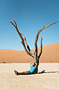 Namibia, Namib Desert, man resting at dead tree in Deadvlei - GEMF000514