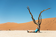 Namibia, Namib Desert, man resting at dead tree in Deadvlei - GEMF000517
