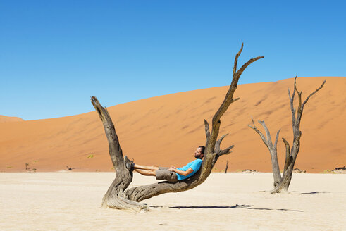 Namibia, Namib Desert, man resting on dead tree in Deadvlei - GEMF000520