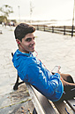 Smiling athlete sitting on bench after training listening to music from smartphone - RAEF000687