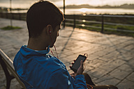 Athlete sitting on bench after training listening to music from smartphone at sunset - RAEF000690