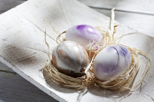 Three nests with Easter eggs on wooden bowl - CSF026855