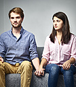 Serious young couple sitting on couch holding hands - DISF002264