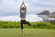 Indonesia, Bali, Tanah Lot, woman practising yoga at the coast - KNTF000186