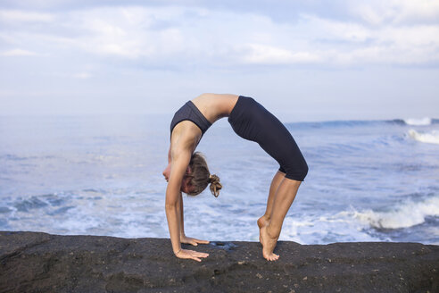 Indonesia, Bali, woman practising yoga at the coast - KNTF000192
