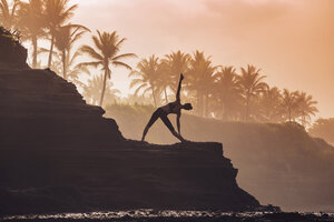 Indonesia, Bali, woman practising yoga at the coast at twilight - KNTF000195