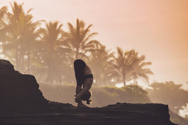 Indonesia, Bali, woman practising yoga at the coast at twilight - KNTF000198