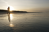 Germany, Langeoog Island, man walking on the beach at sunset - JATF000789