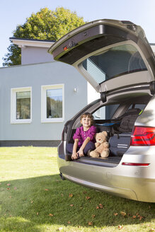 Smiling girl in with teddy bear car boot in front of house - FKF001609