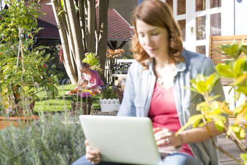 Young woman using laptop in garden with mother and daughter in background - FKF001636