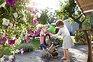 Grandmother and granddaughter washing bicycle on garden terrace - FKF001645
