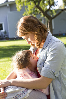 Mother holding daughter in garden - FKF001651