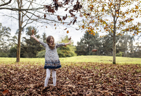 Laughing girl throwing autumn leaves in the air - MGOF001112