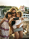 Spain, Menorca, woman and her little daughters taking a selfie with smartphone - MGOF001118