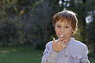 Portrait of happy boy eating sweets - LBF001295