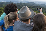 Germany, Siebengebirge, back view of four friends taking a selfie with smartphone on Mount Olivet - PAF001501