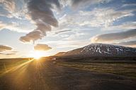 Iceland, car on gravel road under midnight sun - PAF001507