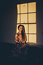 Young woman in floral dress in sunlight in a room - MAUF000125