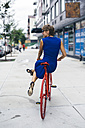 USA, New York City, Williamsburg, back view of smiling blond woman balancing on red bicycle - GIOF000559