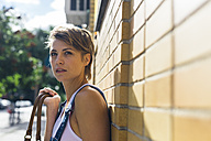 Portrait of waiting blond woman leaning against a wall - GIOF000562