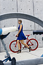 Blond woman with racing cycle on pavement - GIOF000565